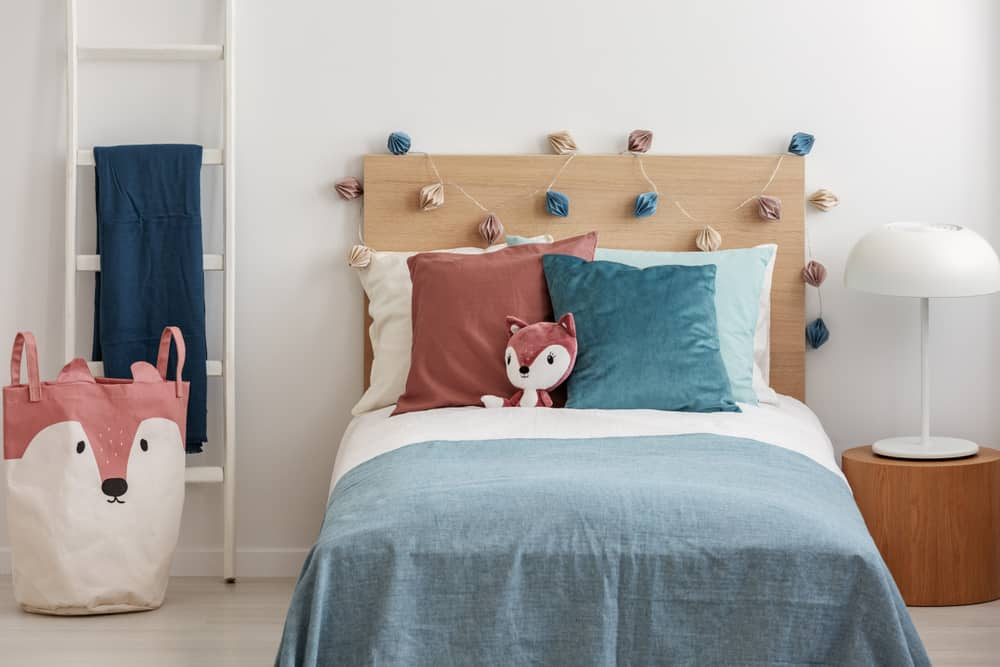 Kid's bed with a velvet pillows and a plush fox.