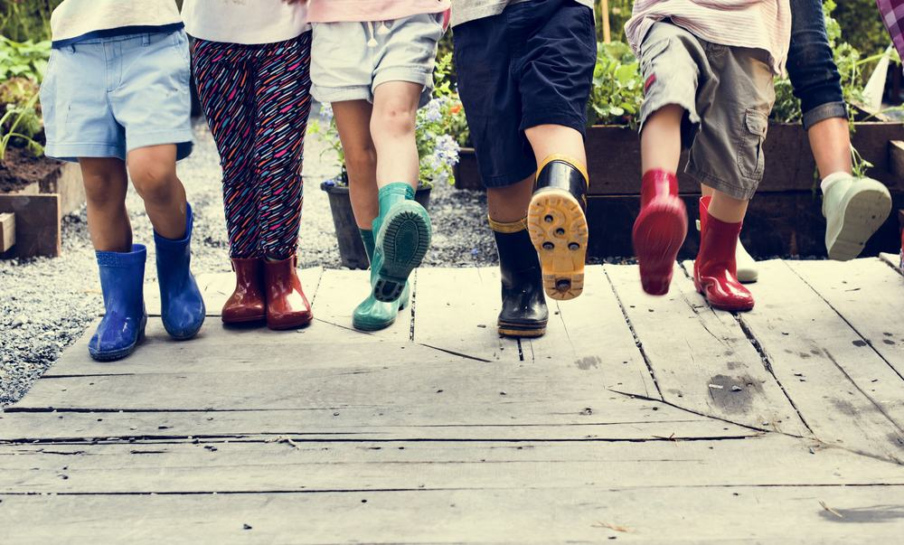 A group of kids wearing rubber boots for gardening.