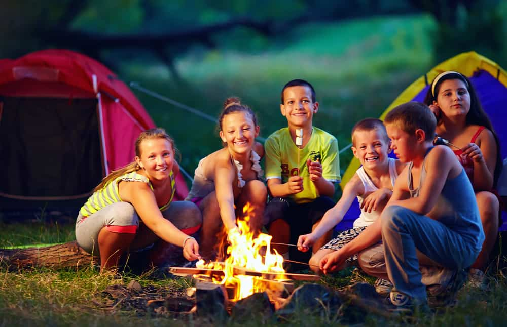 Group of kids roasting marshmallows on campfire.