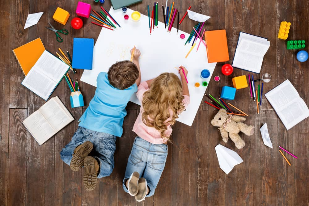 Little boy and girl lying and drawing on a white pad.