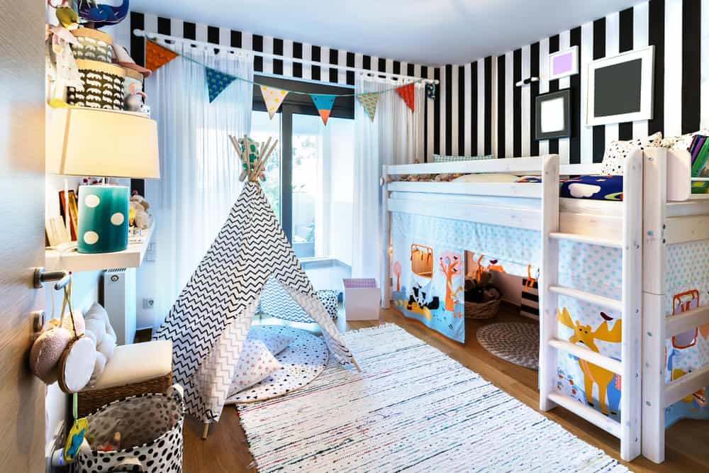 Kid's bedroom with striped walls, a loft bed, a teepee, and a large rug.