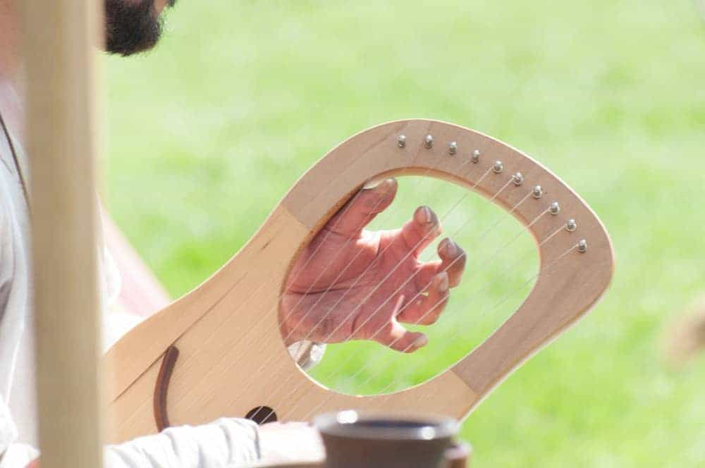 A man playing a medieval harp outdoors.