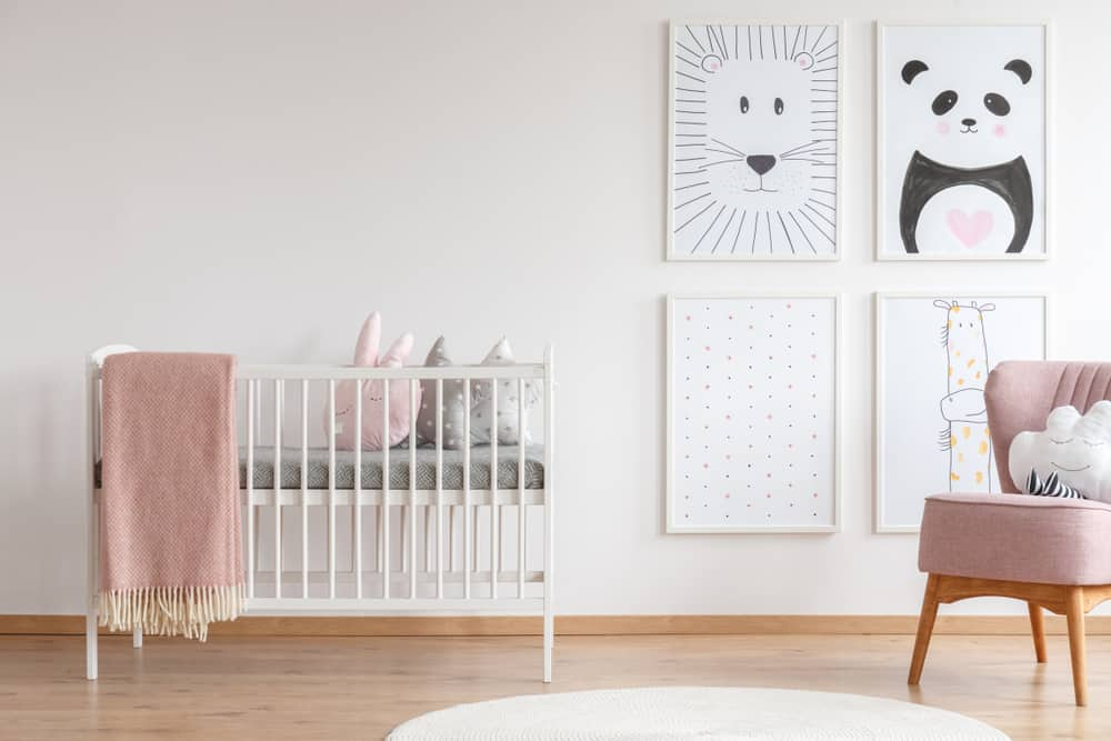 Nursery room with a mini crib, pink upholstered chair, and a cute gallery wall.