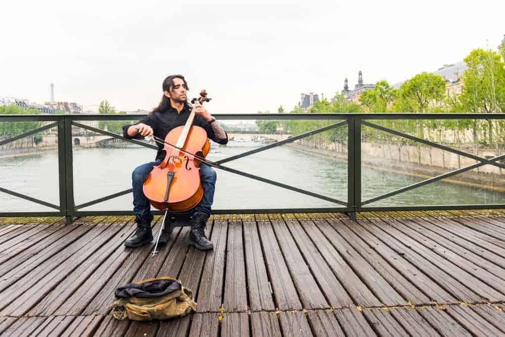 A plays a cello on a scenic wooden bridge.