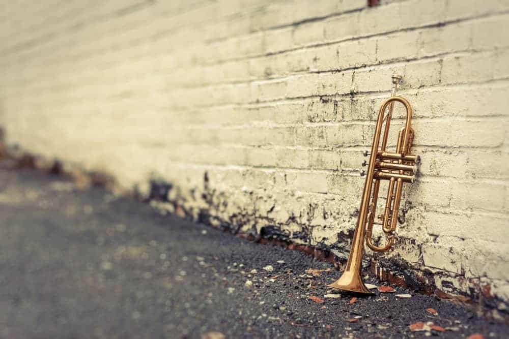 Old trumpet leaning against distressed-looking dirty white brick wall.