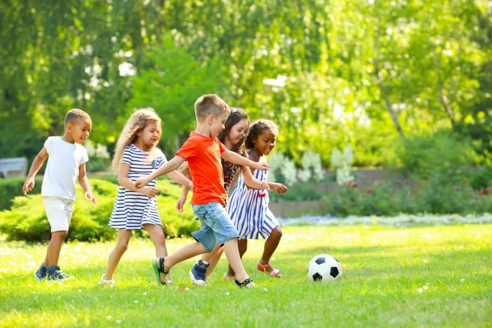 Group of kids playing football outdoors.