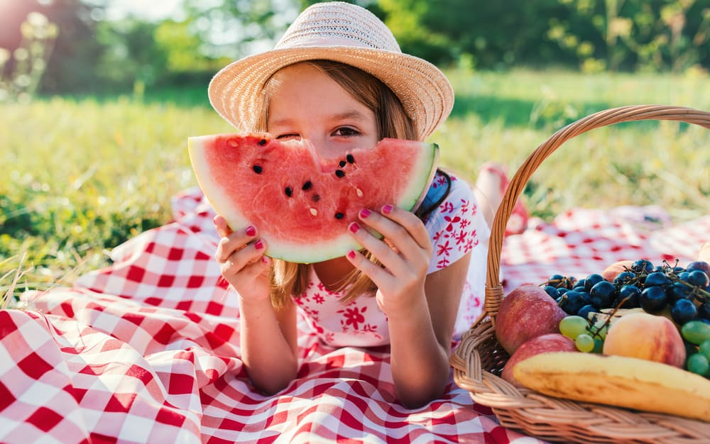 Little girl eating watermelon and enjoying picnic in the park.