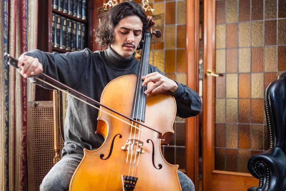 A man plays a cello made of poplar.