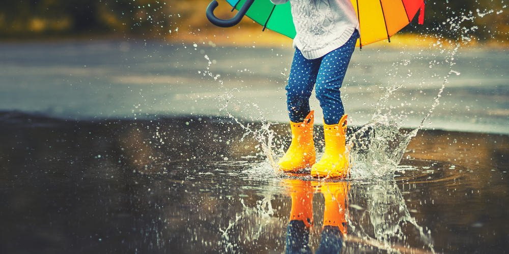 Young girl in yellow rain boots jumping over a puddle.