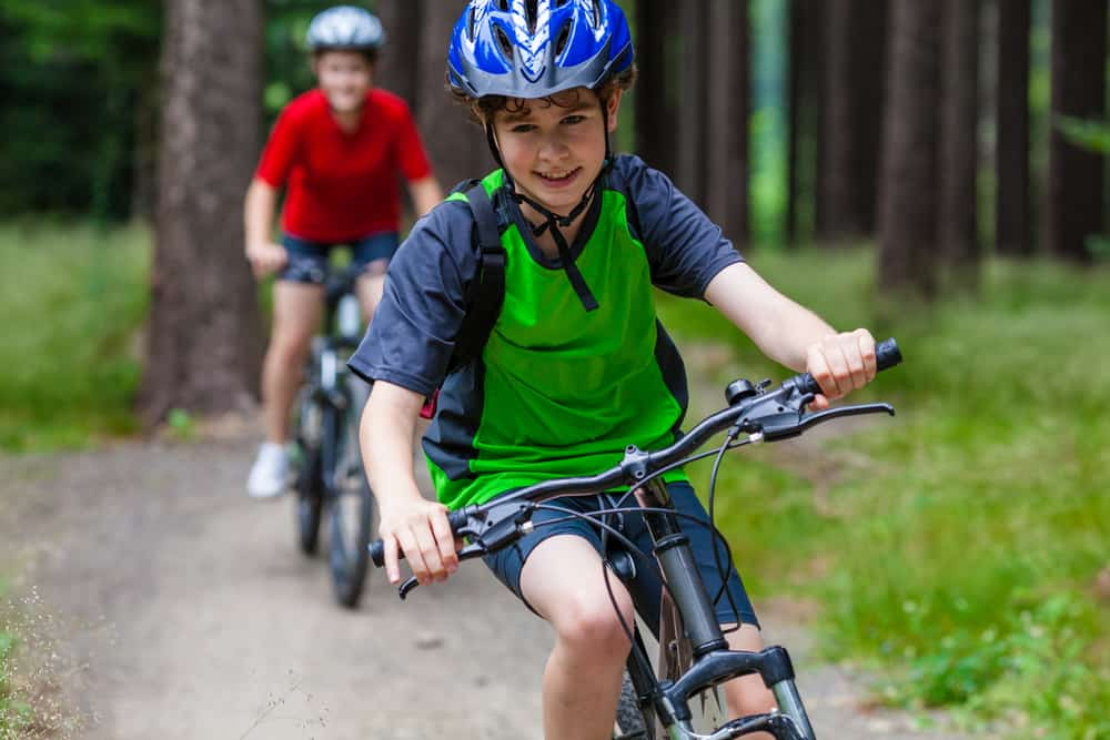 Boys riding bike in the woods.