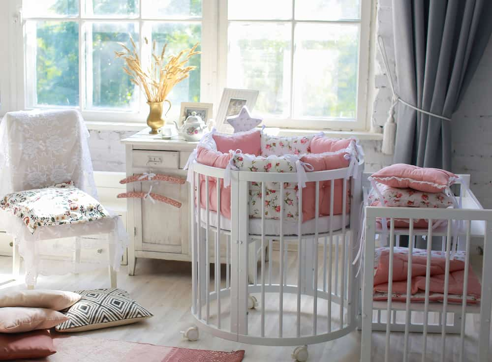 Nursery room with a white chair, a distressed cabinet, and a round crib with wheels.