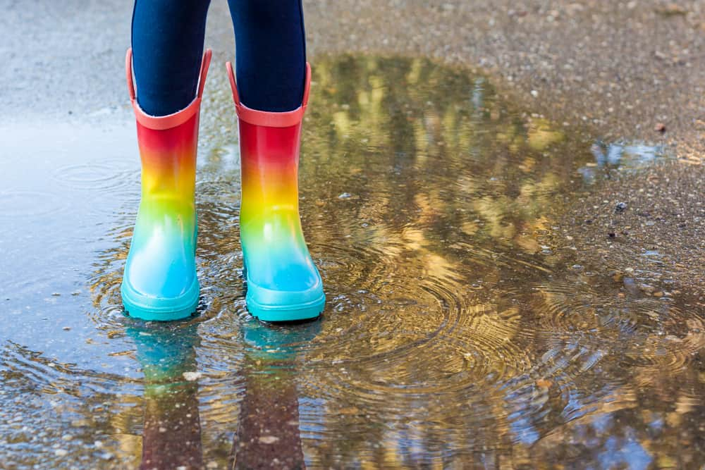 Girl wearing colorful rubber boots standing over a puddle.