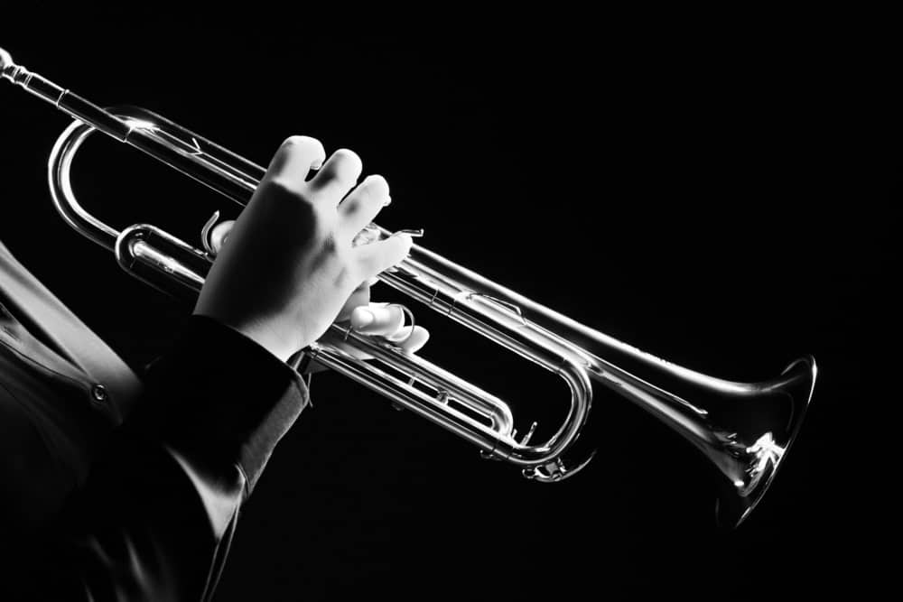 Musician using a trumpet on black background.