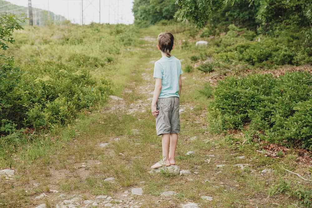 Boy standing on the country road and looking into the distance.