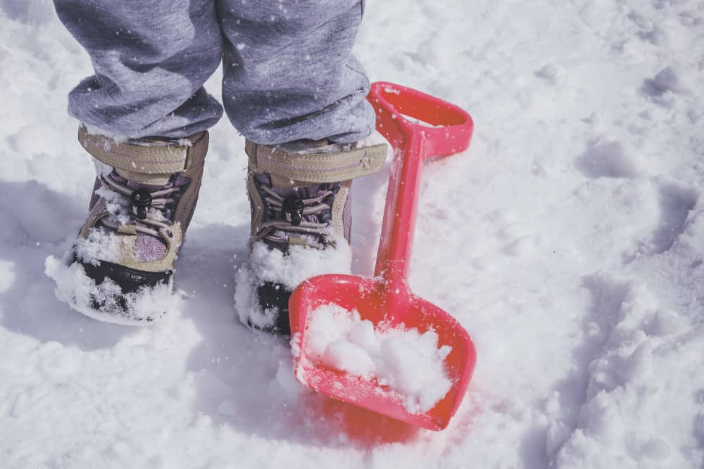 Kid in a snow boot playing with a red shovel.