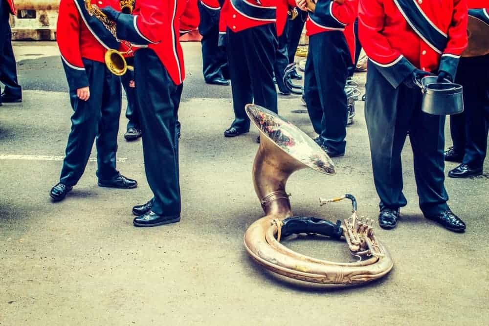 Sousaphone resting on the concrete ground as the marching band stands idly.