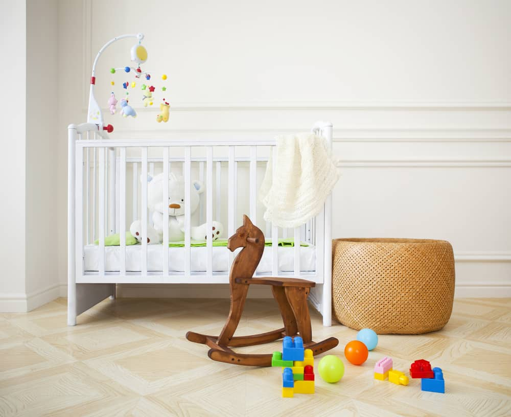 Nursery room with standard crib, wicker ottoman, and a wooden rocking horse.