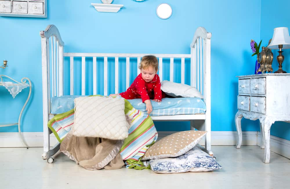 Toddler playing on his bed.