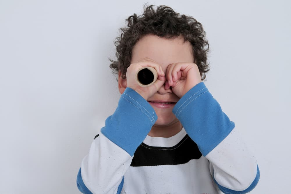 Boy looking through toilet paper roll.
