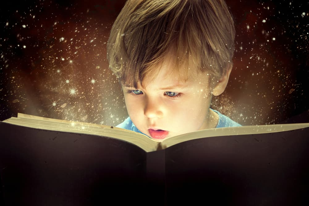 A kid reading a book that lights up.