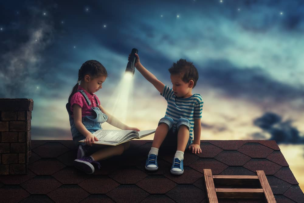 Two kids reading a book on a rooftop.