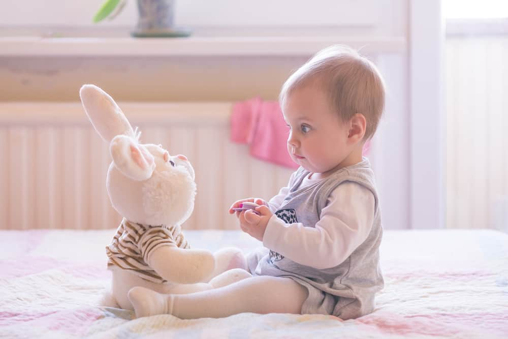 This is a baby girl playing with a stuffed rabbit plush toy.