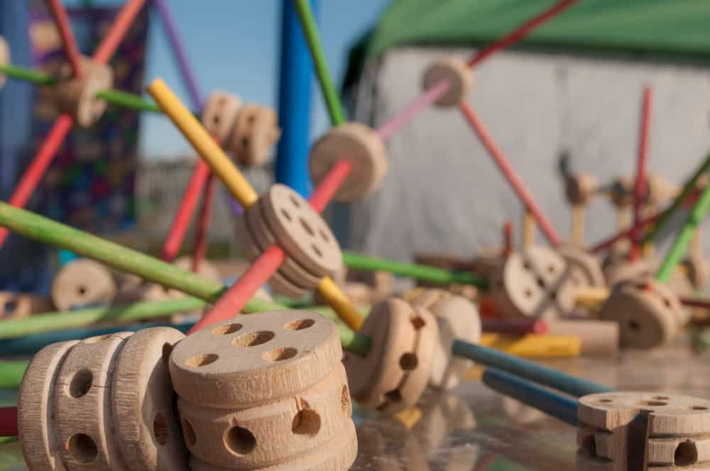 This is a close look at a bunch of wooden vintage tinker toys on the ground.