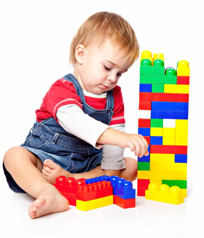 A toddler playing with big colorful building blocks.