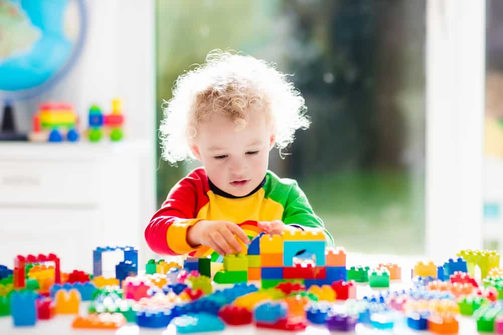 A toddler playing with colorful Lego toys.