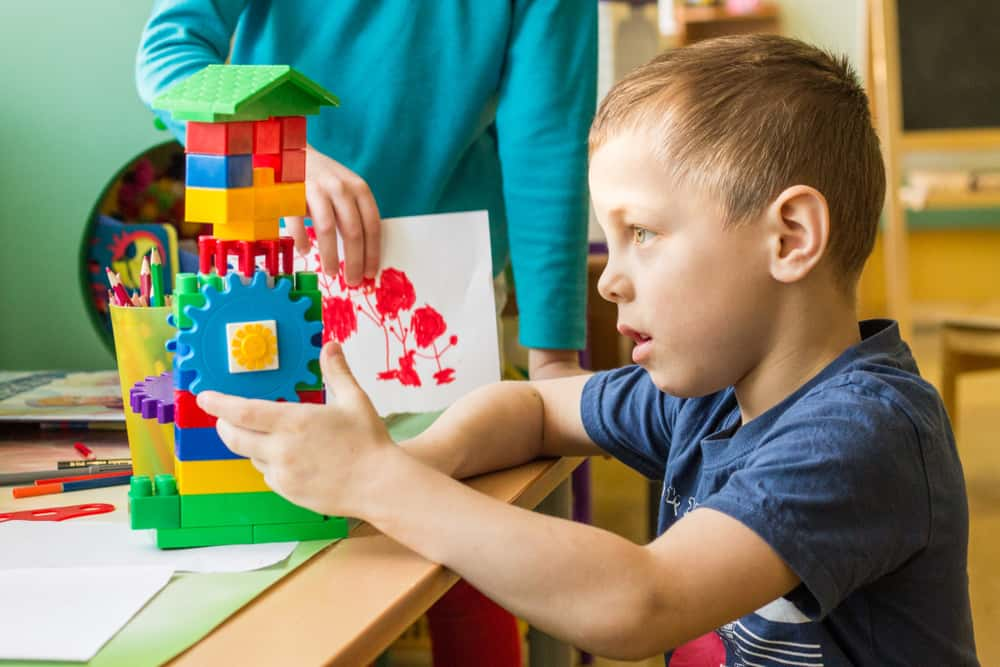 A young boy playing with colorful building blocks.