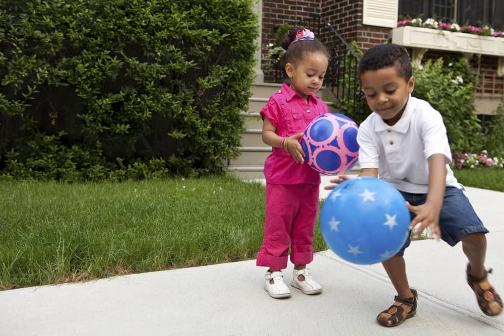 This is a close look at two kids playing with colorful patterned balls.