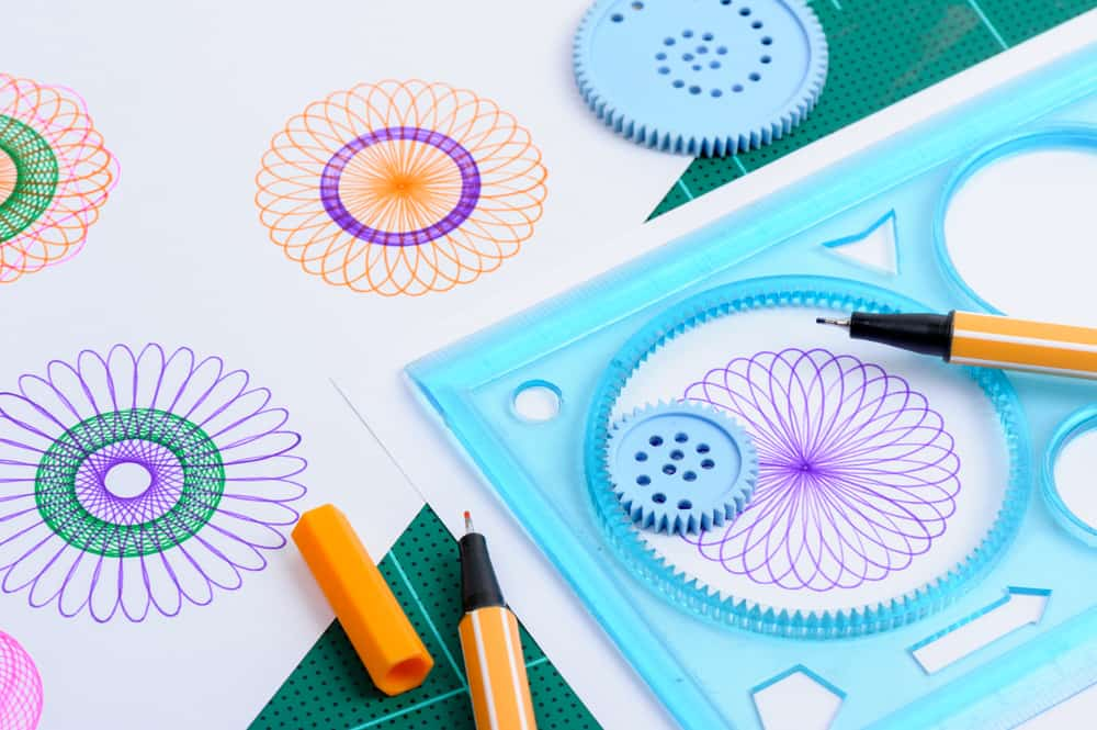 A close look at a Spirograph kit with a few patterns done.