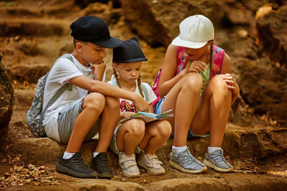 Kids navigating on map during treasure hunt game.