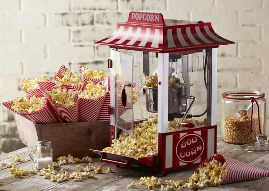 Cute popcorn maker surrounded by cones of popcorn.