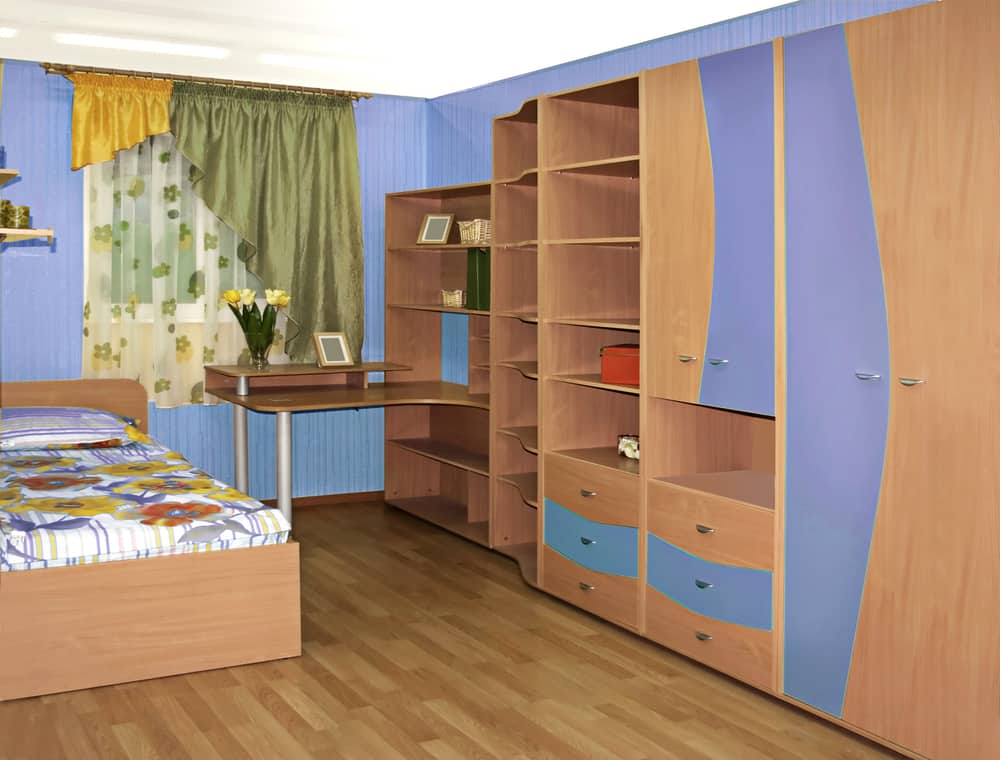 Kid's bedroom with a wardrobe desk and a cozy wooden bed.
