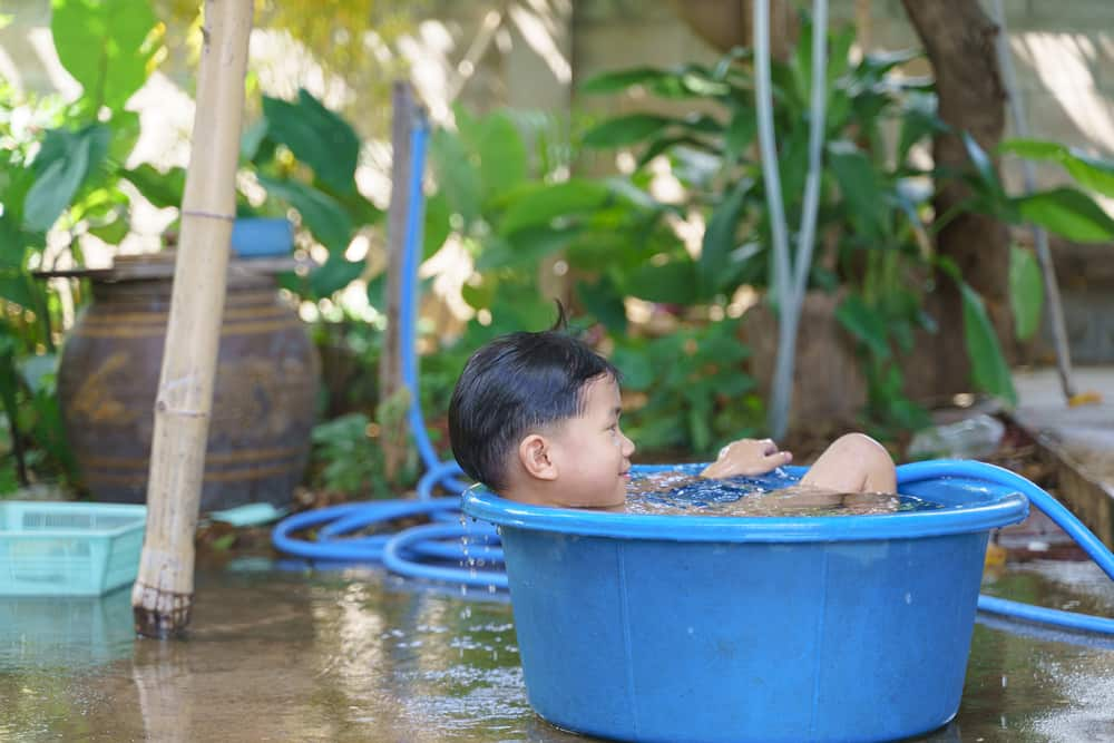 This is a kid soaking in a water basin.