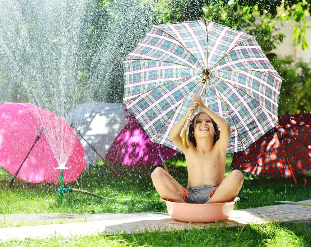 A kid playing with umbrellas and sprinklers.