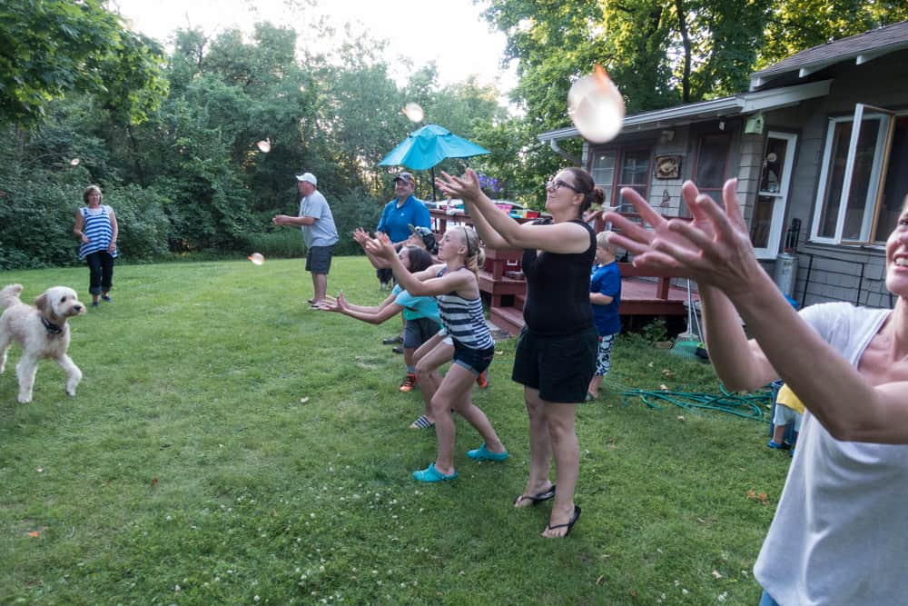 People playing water balloon toss in the yard.