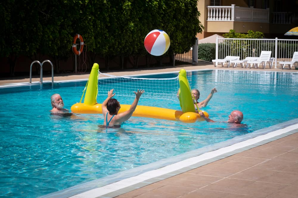 Old people playing volleyball at the pool.