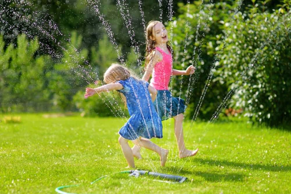 A couple of girls playing with the sprinkler of the grass lawn.