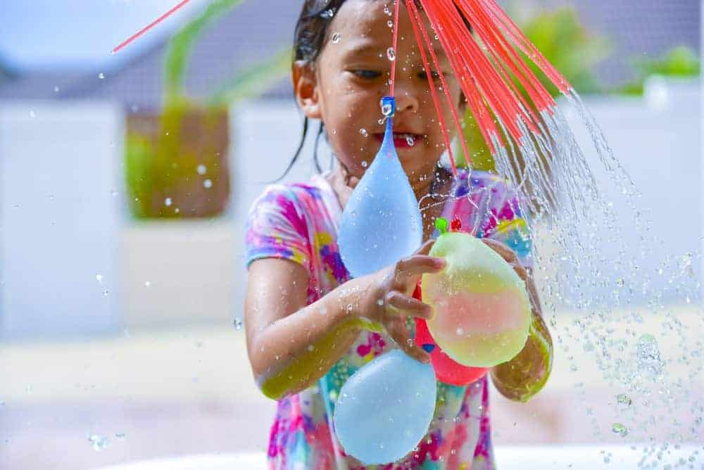 A young girl gets wet while playing with water balloons.