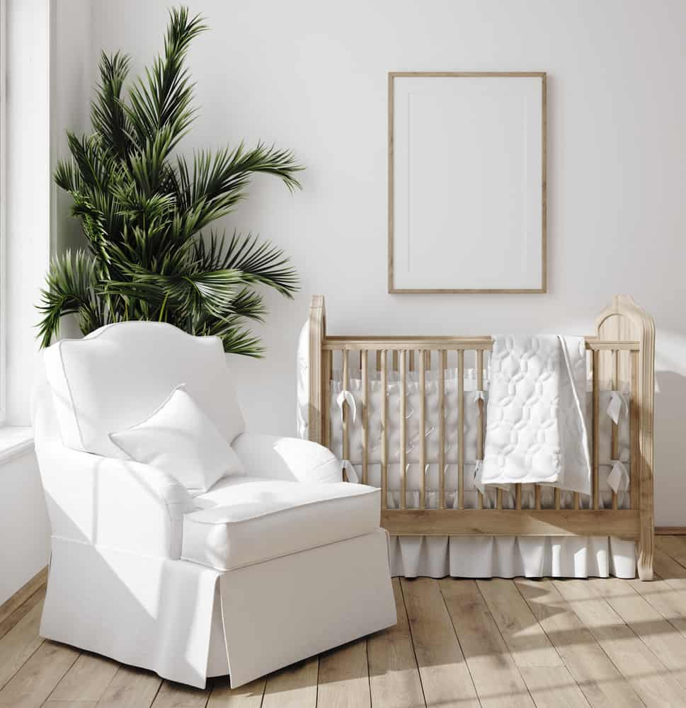 Nursery room with a skirted wooden crib and a white armchair over wide plank flooring.