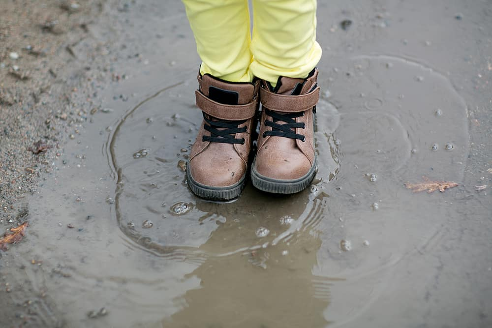 Young boy in work boots standing over a muddy puddle.