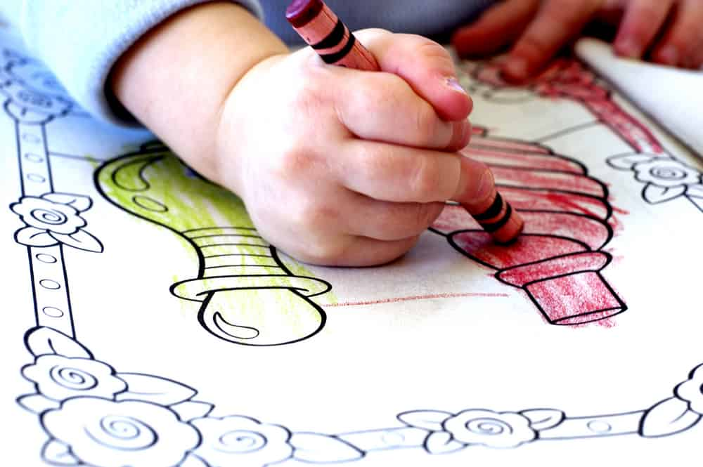 A close look at a child coloring a coloring book.