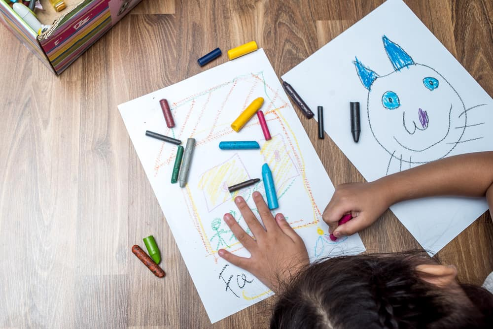 A kid using crayons to color on pieces of paper.