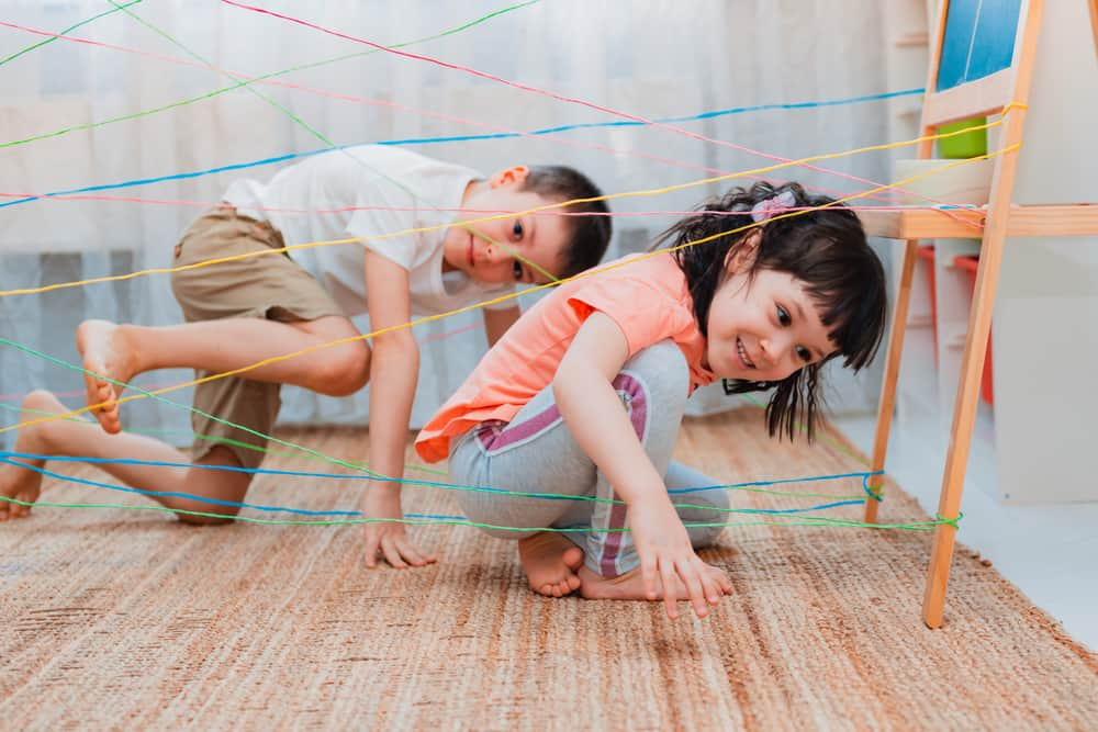 A couple of kids playing indoor obstacle course.