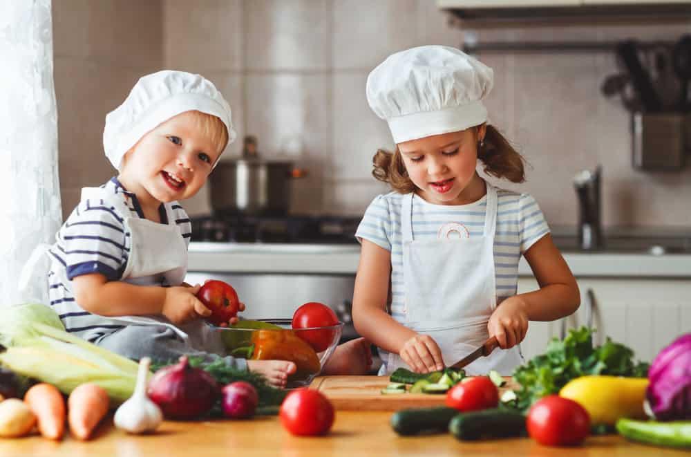 Children preparing vegetables in the kitchen.