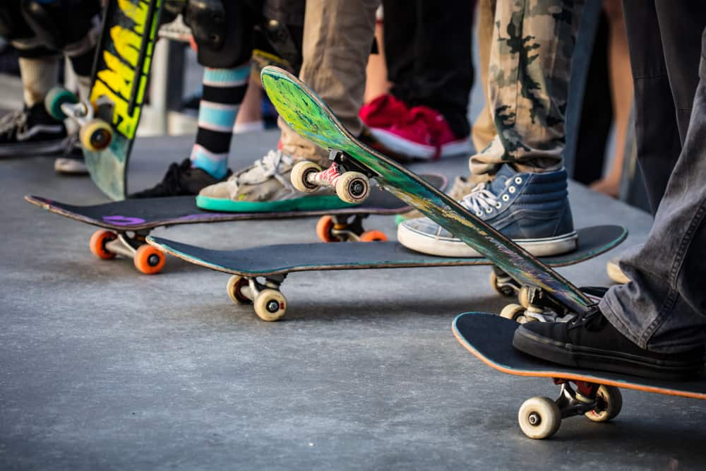 A close look at a row of skateboarders getting ready.