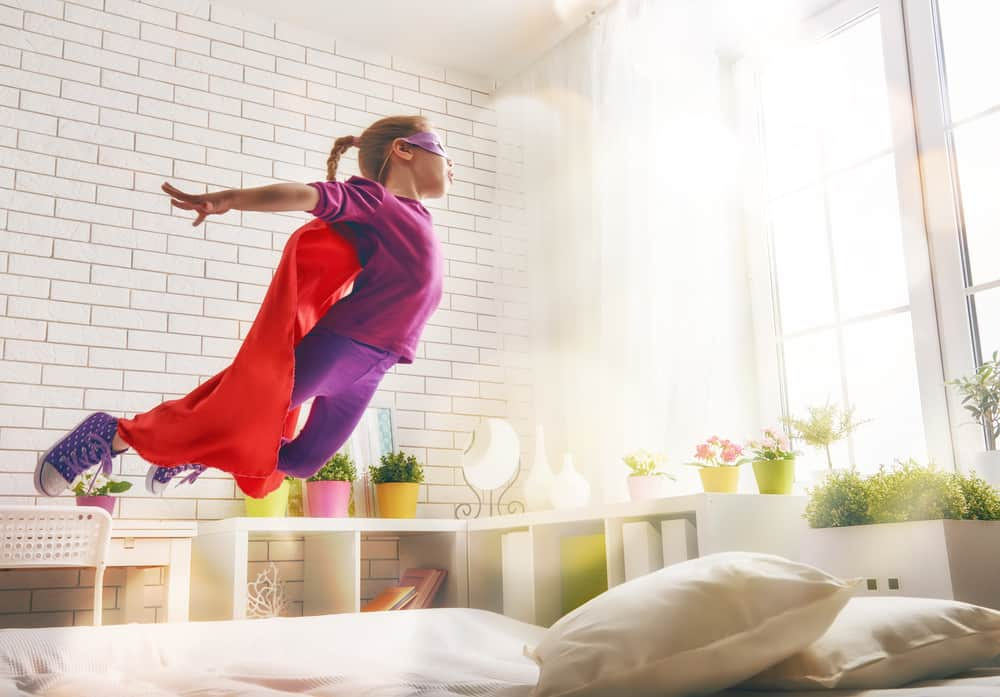 A kid wearing a cape playing superhero in the bedroom.