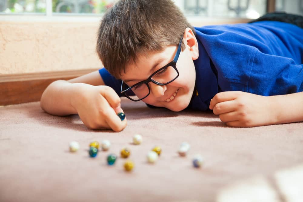 This is a boy playing with marbles on a carpeted floor.